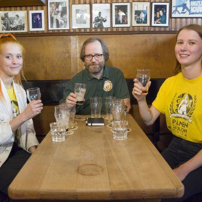 Kaksi naista ja yksi mies Salhojankadun pubissa olutlasit kädessään.