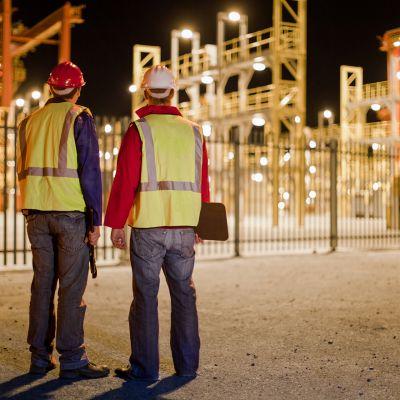 kaksi kypäräpäistä työläistä teollisuuslaitoksen edustalla