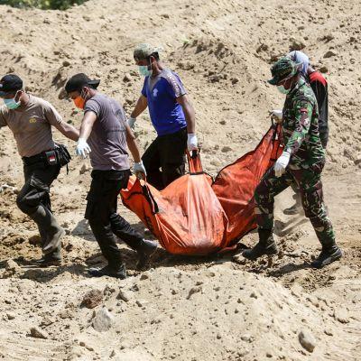 Pelastajat kantavat ruumiita Palussa haudattaviksi.