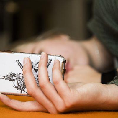 Tyttö makaa sohvalla ja katselee kännykkää.