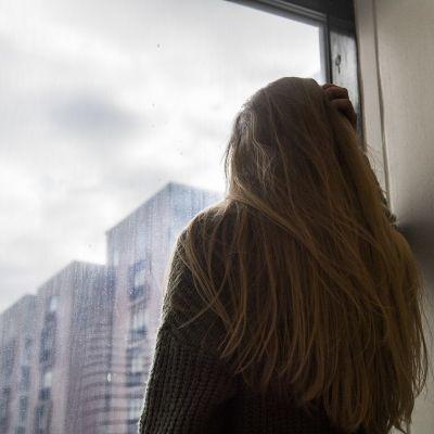 Tyttö katselee ikkunasta ulos.