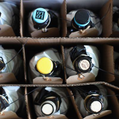 Pakattuja viinipulloja pahvilaatikossa.