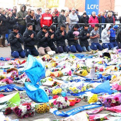 Thaimaan Chaiyaphumin Fox Hunt Football Academyn pelaajat kunnioittavat helikopteriturman uhreja King Power -stadionin ulkopuolella.