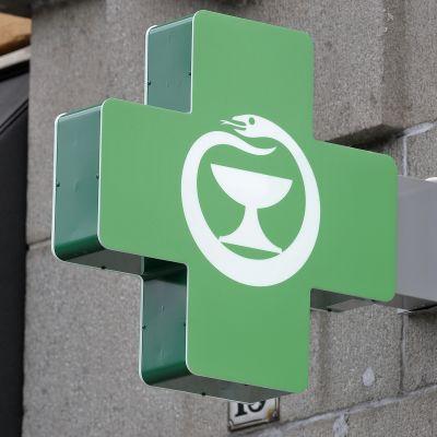 apteekin logo talon seinässä