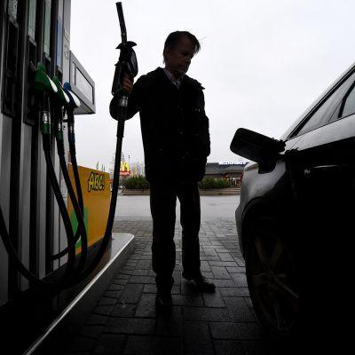 mies huoltoasemalla bensapistooli kädessä