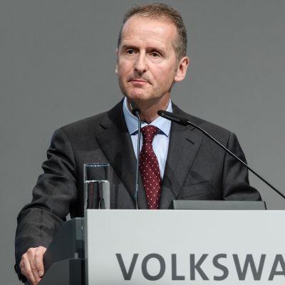Volkswagenin toimitusjohtaja Herbert Diess puhuu puhujanpöntöstä, jonka etuosassa lukee Volkswagen.