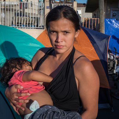 Hondurasilainen Gabriela Regaldo, 20 vuotta, on osa siirtolaiskaravaania. Hän asuu teltassa Tijuanassa kahden taaperoikäisen lapsensa  kanssa. Sylissään hänellä on 1,5 vuotias tytär, Sofia.