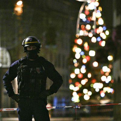 Ranskalainen poliisi seisoo vartiossa Strasbourgissa tiistai-iltana 11. joulukuuta. Takana monivärinen joulukuusi.