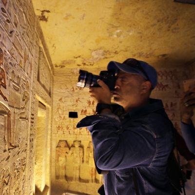 Valokuvaaja taltioi hautakirjoituksia.