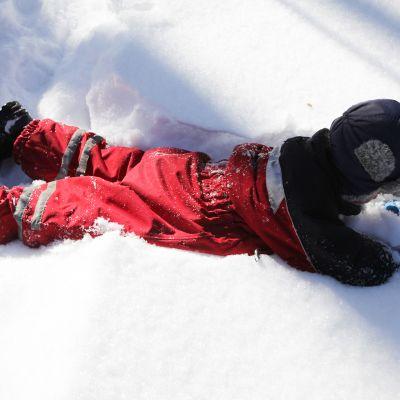 Lapsi leikkii lumihangessa.