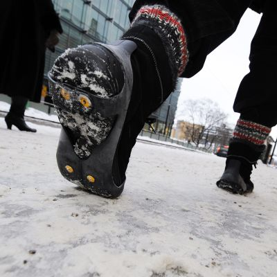 Jalankulkija kävelee liukkaalla jalkakäytävällä