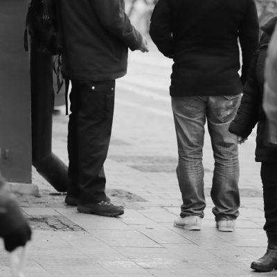 Miehet seisovat kävelykadulla.