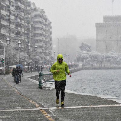 Mies lenkkeilee Kreikan Thessalonikissa 4. tammikuuta. Sataa märkää lunta.