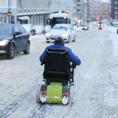 Mies ajaa tiellä invamopolla.