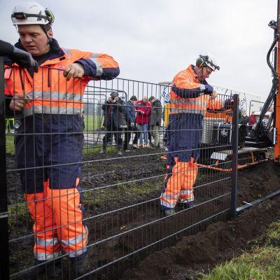 Työntekijät pystyttävät 1,5-metristä verkkoaitaa