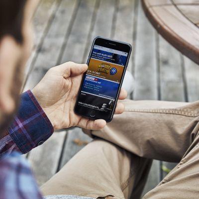 Mies selaa mobiilipelejä kännykästä.