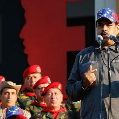 Lippalakkipäinen Nicolas Maduro pitää puhetta, vasemmalla maastopukuista yleisöä.