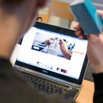 Mies selaa verkkopankkia avainlukulista kädessään.