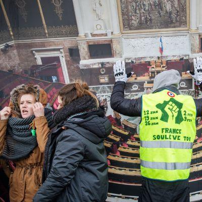 Keltaliivinen mielenosoittaja osoittaa mieltänsä tänään Pariisissa kuvan edessä joka esittää Ranskan parlamentin palatsia.