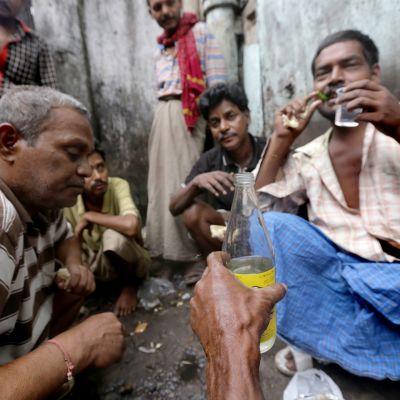 Itsevalmistettua maalaisviinaa juodaan kadulla Kalkutassa.
