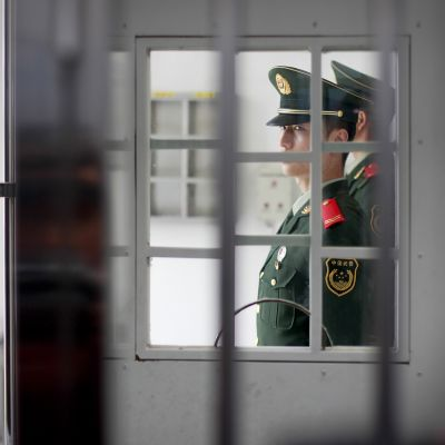 Vartija seisoo vankilan pääsisäänkäynnin luona.
