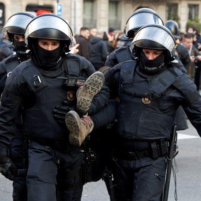 Poliisit kantoivat tien tukkimiseen osallistunutta lakkoilijaa torstaina Barcelonan keskustassa.