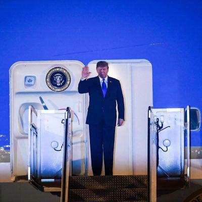 Donald Trump seisoo koneen ovella portaiden yläpäässä puvussa ja sinisessä kravatissa ovella vilkuttaen oikealla kädellään. Koneen sininen väri ja valaistus tekevät kuvasta muutenkin sinivärisen.