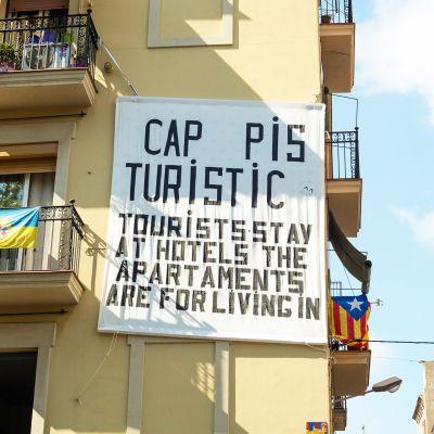 Talon seinään ripustettu lakana kehottaa turisteja yöpymään hotelleissa.