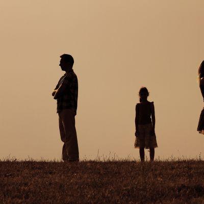 Silhuettikuva äidistä, isäsätä ja lapsesta.