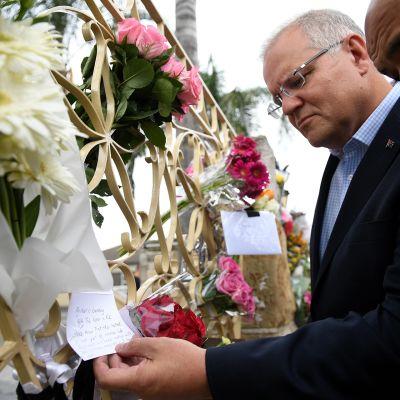 Australian pääministeri Scott Morrison tutkii terrori-iskun uhrien muistoksi tuotuja viestejä ja kukkia.