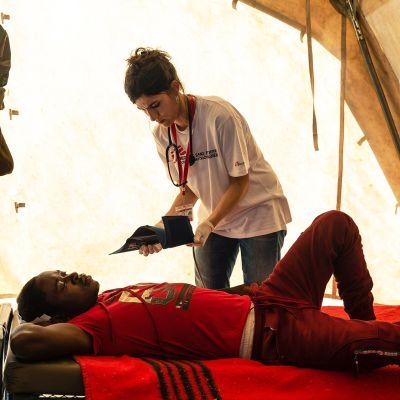 Lääkäri tutkii loukkaantunutta miestä kenttäsairaalassa.