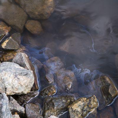 Bild på en bäck och stenar, på vattenytan syns skimrande olja.