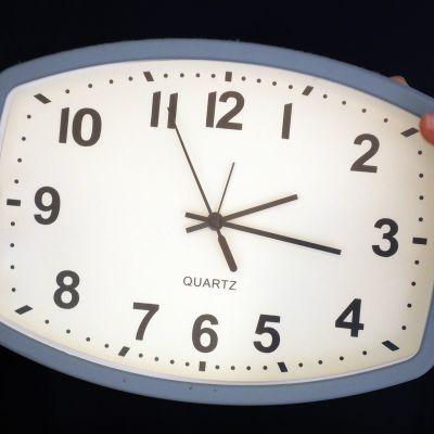 Kädet pitävät herätyskelloa.