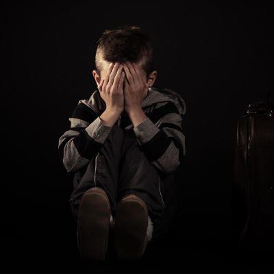 Nuori poika nojaa päätään käsiinsä.