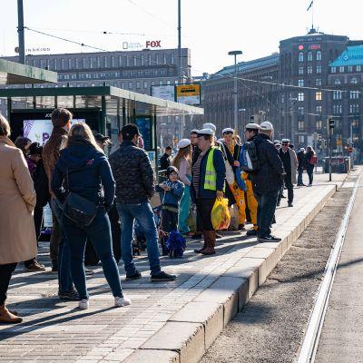 Ihmisiä jonottamassa ratikkaa Helsingin rautatieaseman luona.