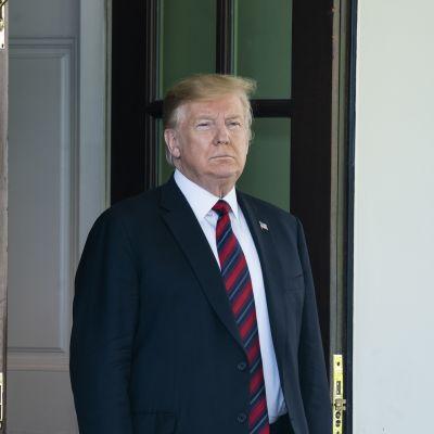 Yhdysvaltain presidentti Donald Trump katselee ovelta ulos.