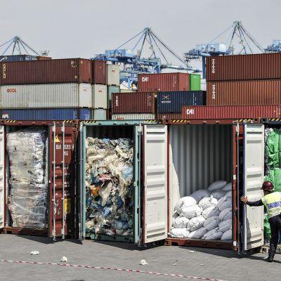 Poliisiviranomaiset tarkastavat muovijätekonttien sisällöt ennen alkuperäismaahan takaisin lähettämistä Port Klangin satamassa Malesiassa 28. toukokuuta.