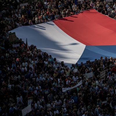 Ihmiset kantoivat Tšekin lippua mielenosoituksessa Prahassa tiistaina.