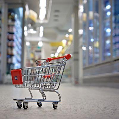 Tyhjä ostoskärry kaupan käytävällä.