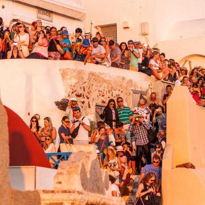 Turistit odottavat auringonlaskua Santorinilla.