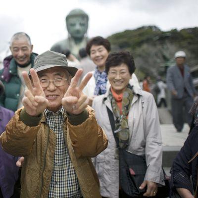 Vanhukset poseeravat Budha-patsaan edustalla Japanissa.