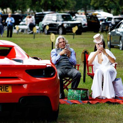 Harmaahiuksinen mies ja valkoisiin pukeutunut nainen istuvat punaisilla ohjajantuolilla ja näppäilevät puhelimiaan. Heidän vierellä vasemmalla on punainen Ferrari.