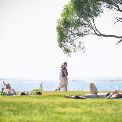 Ihmiset nauttivat lämpimästä kesäkelistä uimarannalla.