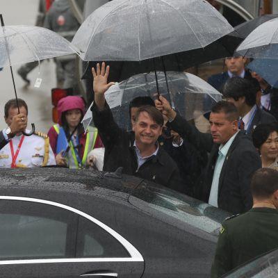 Jair Bolsonaro ja useita muita ihmisiä sateenvarjojen alla lentokentällä.