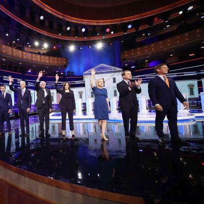 Demokraattien tv-väittelyyn osallistuvat ehdokkaat vilkuttavat lavalla tv-studiossa.