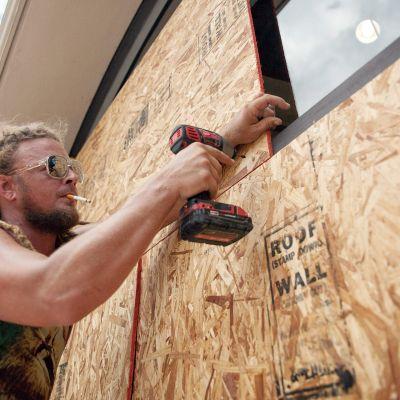 Matt Harrington asentaa vanerilevyjä kauppansa suojaksi.