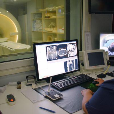 Röntgenhoitaja Viivi Hyvönen tarkkailee magneettikuvauksen kulkua monitorien avulla.