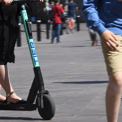 Nainen huristaa sähköpotkulaudalla jalankulkijan takaa.