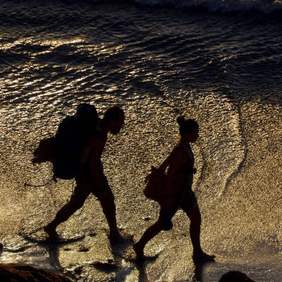 Kaksi reppureissaajaa kulkee rannalla.