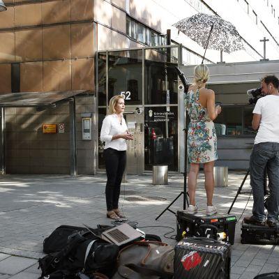 Toimittaja puhuu kameralle  Kronobergin vankilan edustalla Tukholmassa.